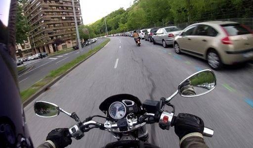 Una moto circula demasiado cerca de coches estacionados.