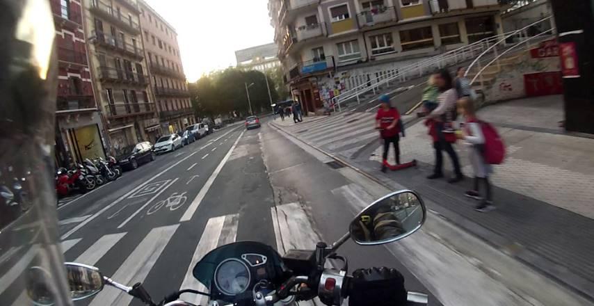 Una moto circula por una calle rodeada de potenciales riesgos