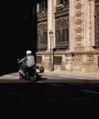 Una moto circula por una calle con poca luz