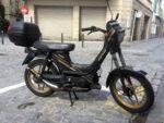 Ciclomotor con pedales aparcado en la calle