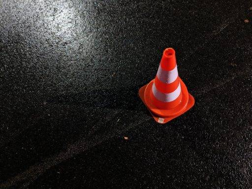 Un cono de obra sobre asfalto mojado