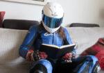 Motorista equipado leyendo un libro en un sofá