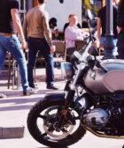 Moto aparcada en primer plano, y varias personas paseando o sentadas en una terraza en el fondo