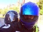 Padre e hijo miran a cámara subidos en una moto