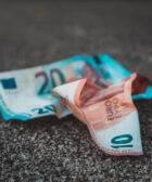 Imagen con dos billetes de euro posados sobre asfalto