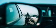 Motocicleta reflejada en el retrovisor de un coche