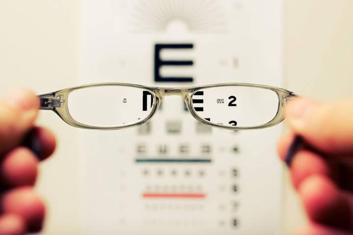 Unas gafas delante de una pared con letras para un test de vista